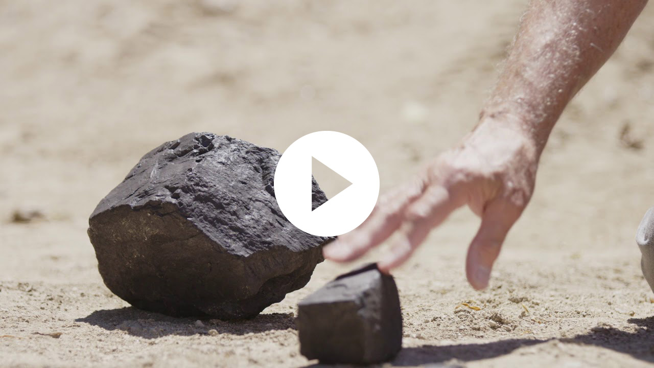 man's hand reaching out to a piece of coal