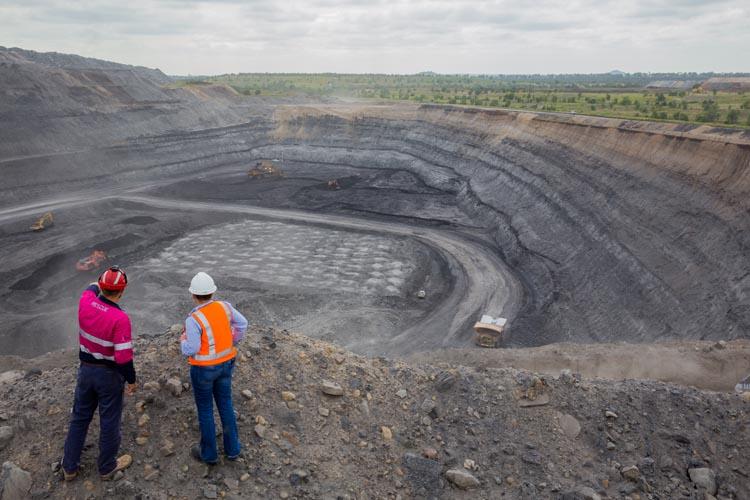 coal workers overlooking open-cut coal mine pit