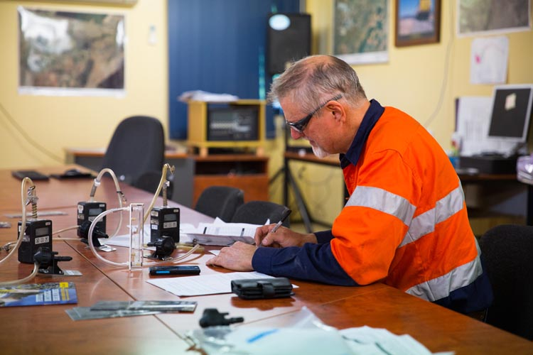 Worker recording results from dust monitoring